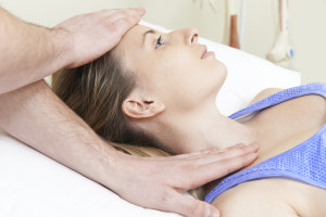 Male Osteopath Treating Female Patient With Neck Problem